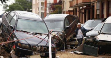 Una mujer habla por teléfono junto a unos vehículo dañados por la fuerza de la riada en Tafalla. - SUSANA VERA