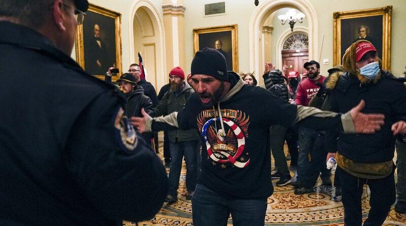 Los manifestantes hacen un gesto a la Policía del Capitolio de los Estados Unidos en el pasillo fuera de la cámara del Senado dentro del Capitolio el miércoles. Manuel Balce Ceneta / AP